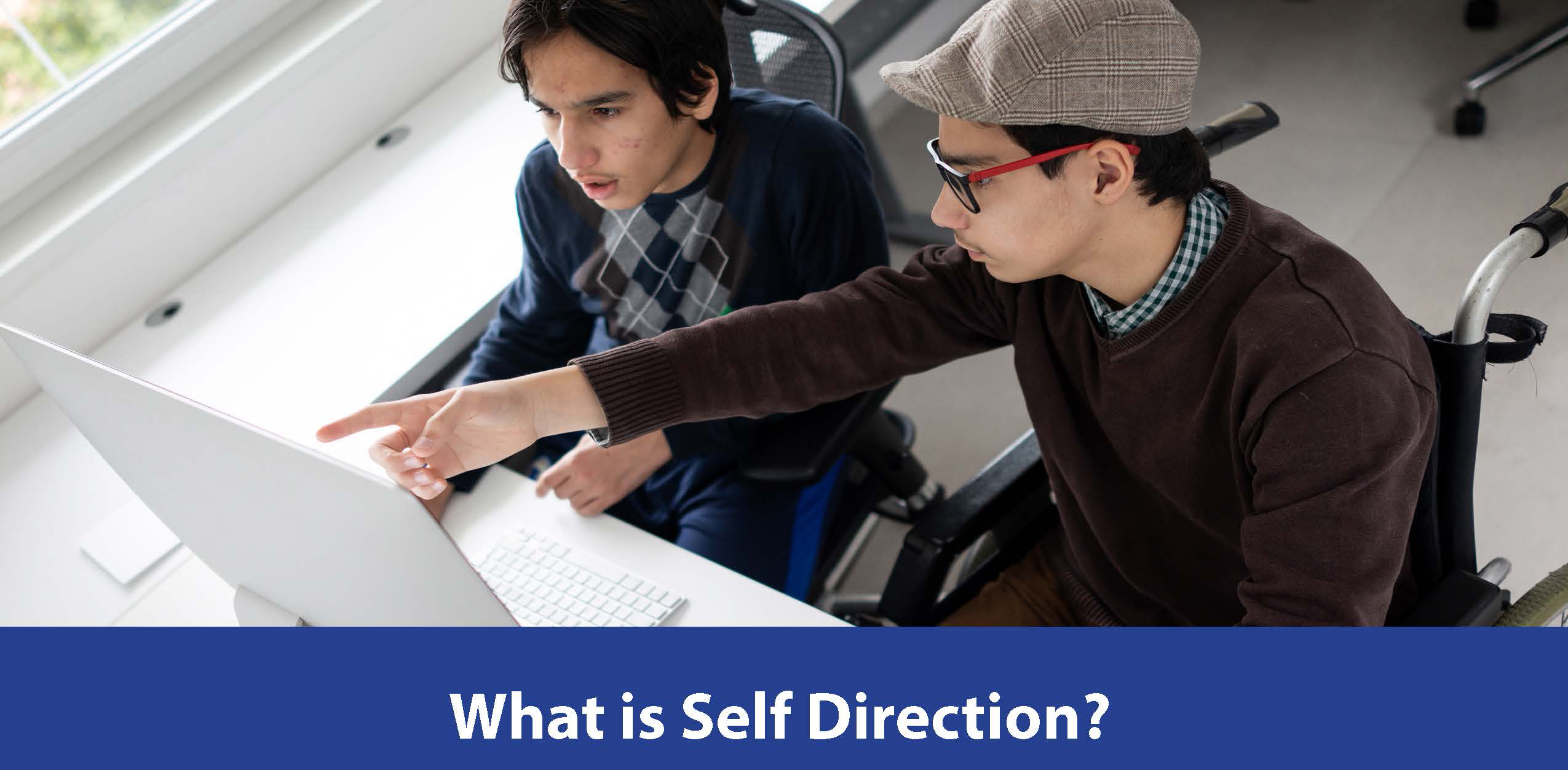 photo of two students sitting at a desk looking at a computer and the words What is Self Direction? Underneath.
