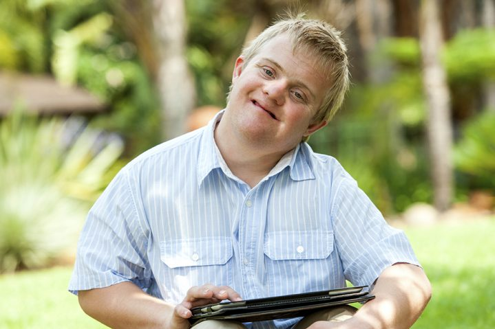 Boy with down syndrome with a tablet.