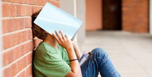 boy hiding his face behind a book