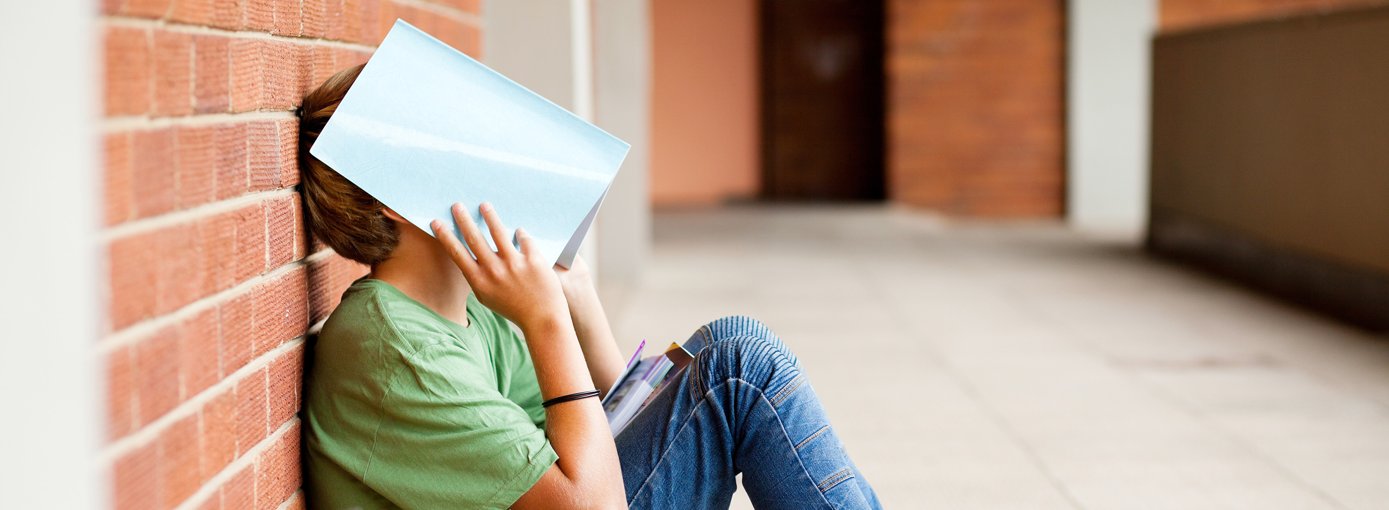 Frustrated teen with face in book