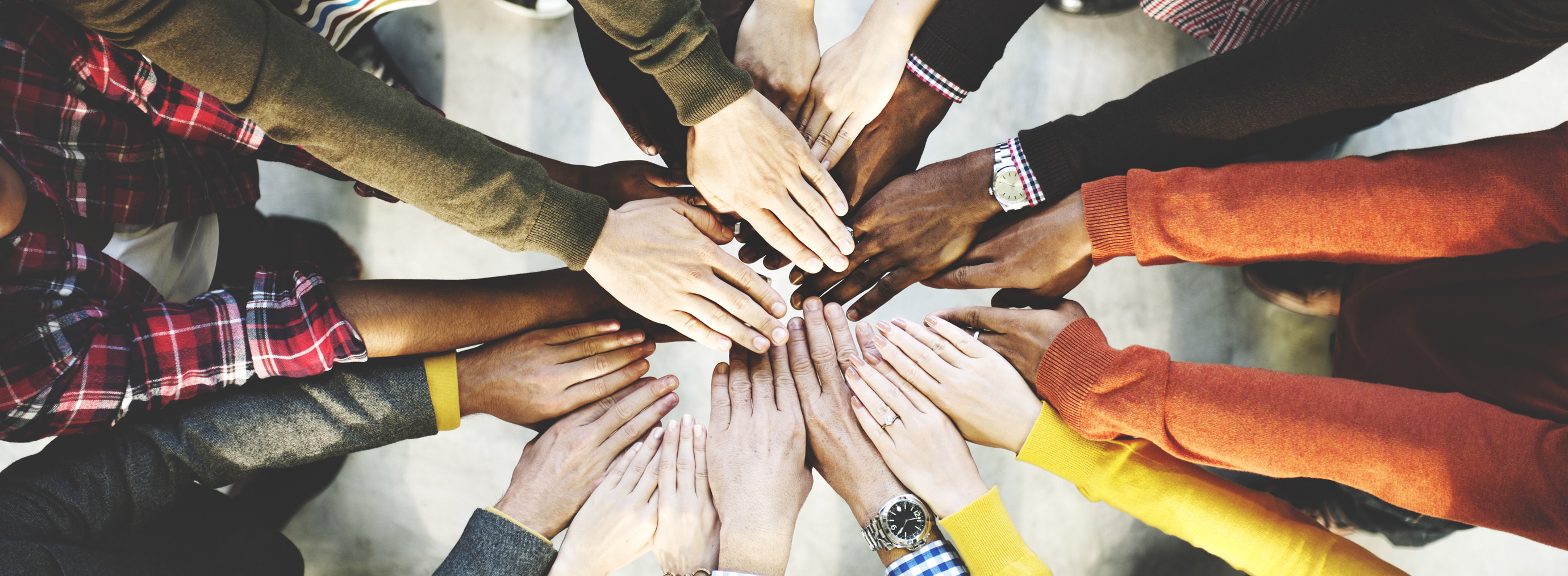 Group of people with their hands in a circle together