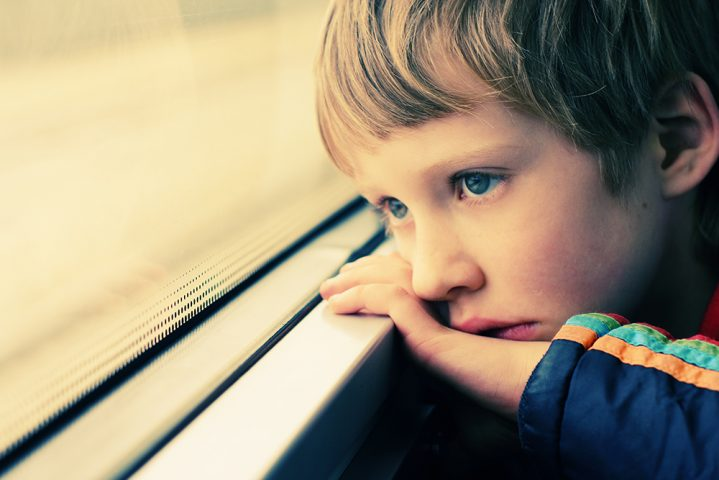boy looking out the window looking sad