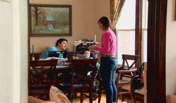Man, woman and child in a wheelchair around dining room table