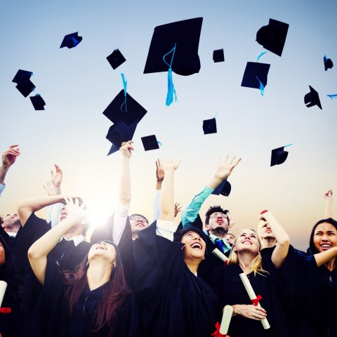 group of graduates throwing caps into the air