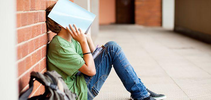 boy hiding behind book