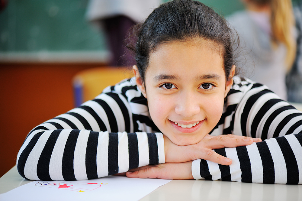young girl in a black & white striped shirt at desk in school with her head resting on her hands and she is smiling.