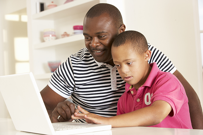 child and father sitting in front of a computer