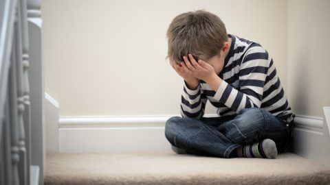 Boy crying on the stairs