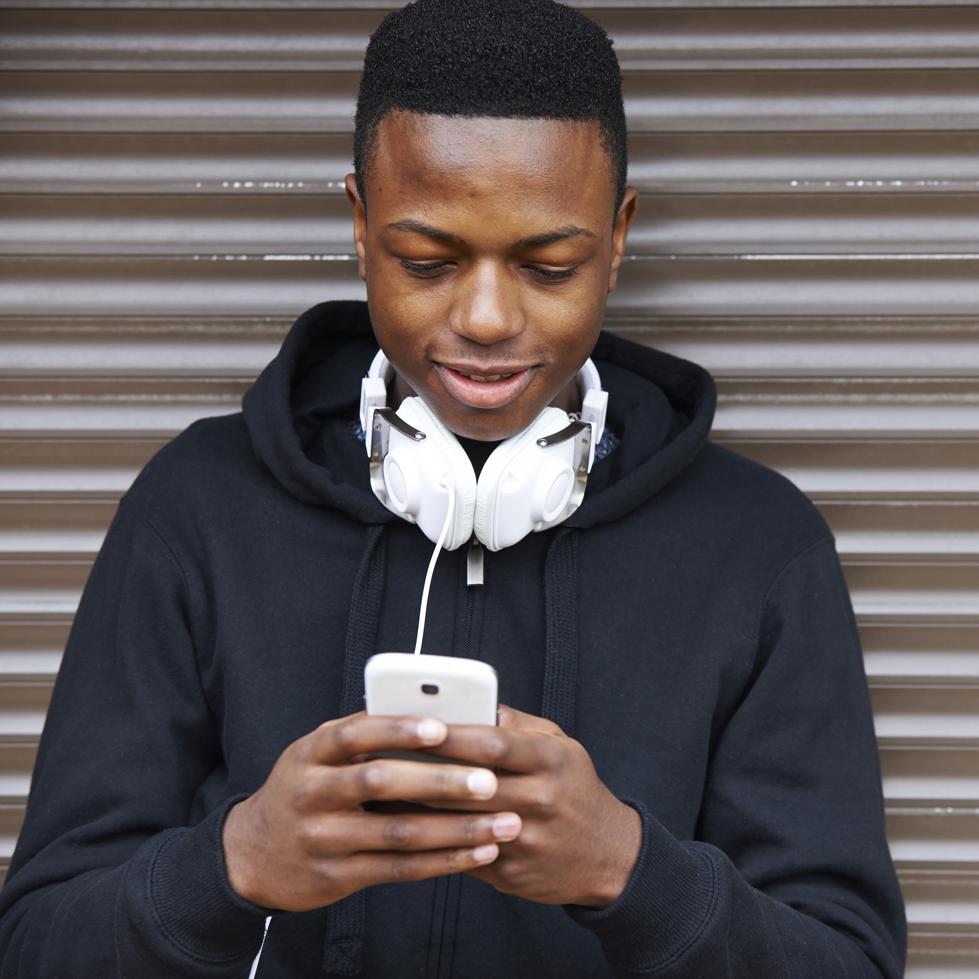 Boy with headphones around his neck checking his phone