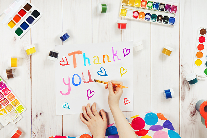 photo of a child's hands with paint and paint brushes making a Thank You sign.